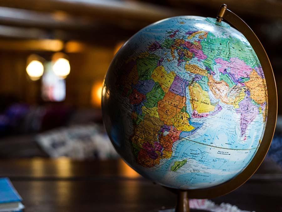 A globe of the world sit on top of a desk in a dark lit room