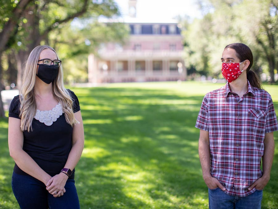 Kyra Morgan and Paul Hurtado stand on the quad wearing masks.