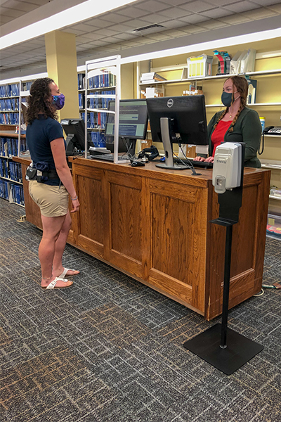 A dark-haired student wearing a face covering stands at the DeLaMare Circulation desk as a DeLaMare staff member wearing a face covering retreives the student's checked-out library materials.