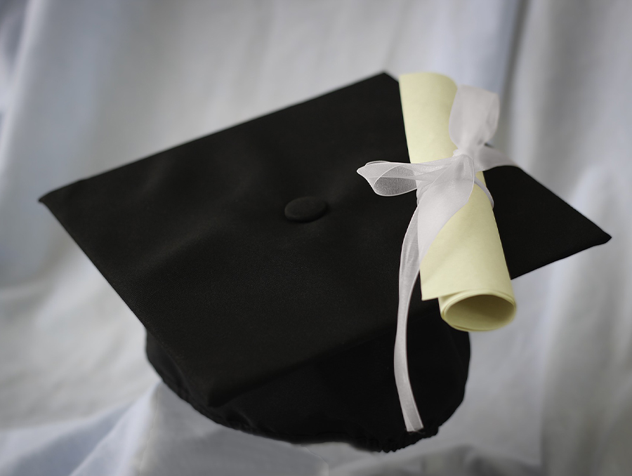 Stock image of a black graduation cap with a diploma on top behind a white background.