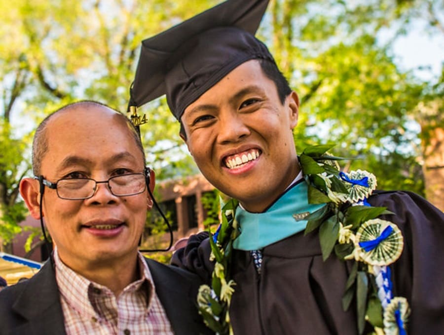 A father with his graduating son in full commencement regalia