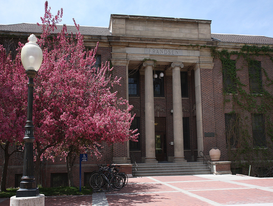 Frandsen Humanities Building with a pink tree out front during the spring