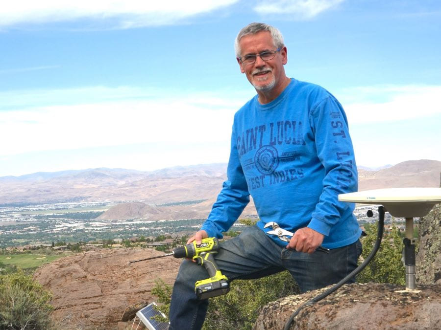 Professor Geoff Blewitt sits alongside a GPS station on a mountain that overlooks the valley of Reno and Sparks, Nev.