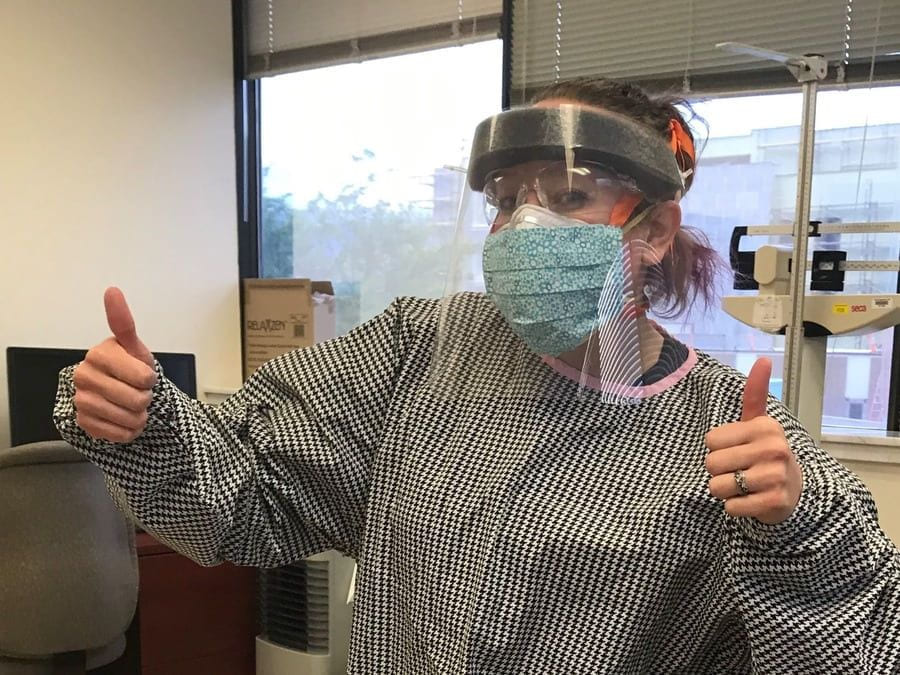 A healthcare worker wearing a gown, face mask, and face shield giving the thumbs up