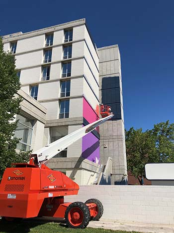 Mural artist Rafael Blanco begins work on a mural on the Sierra Hall building at the University of Nevada, Reno.