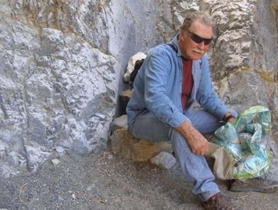 Photo of Tommy Thompson sitting at the base of a rock face holding a map.