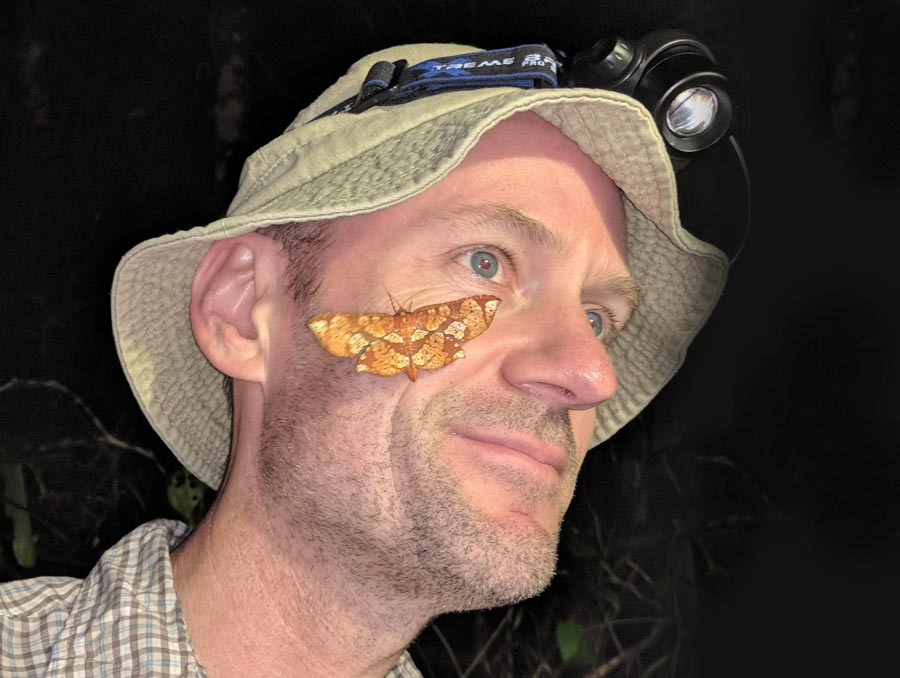 Photo of Matt Forister with a butterfly on his cheek.