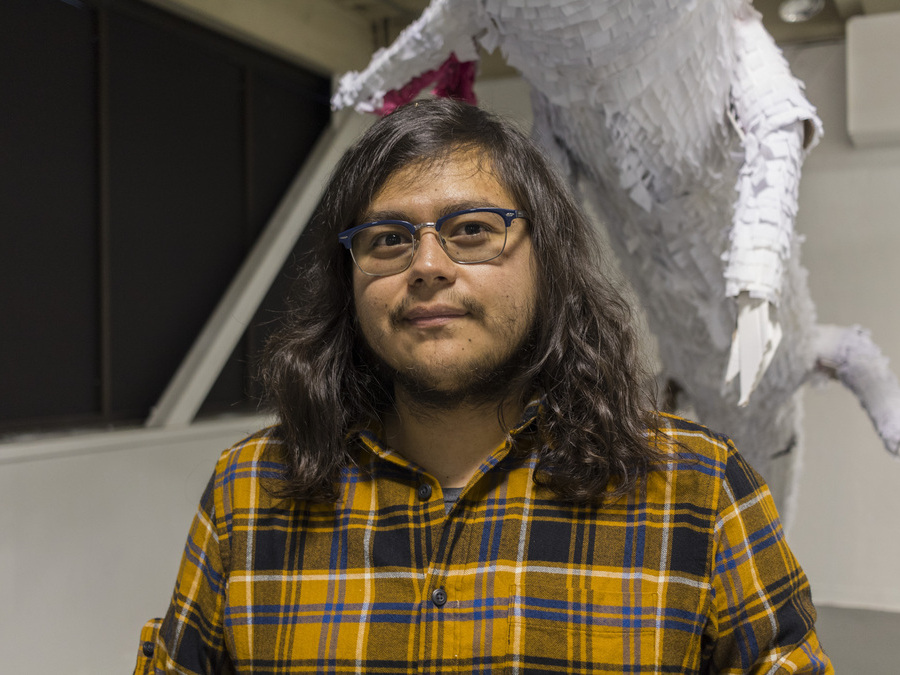 Undergraduate Research awardee Cesar Piedra stands in front of his sculptural project: a white animal figure with a textured paper surface.