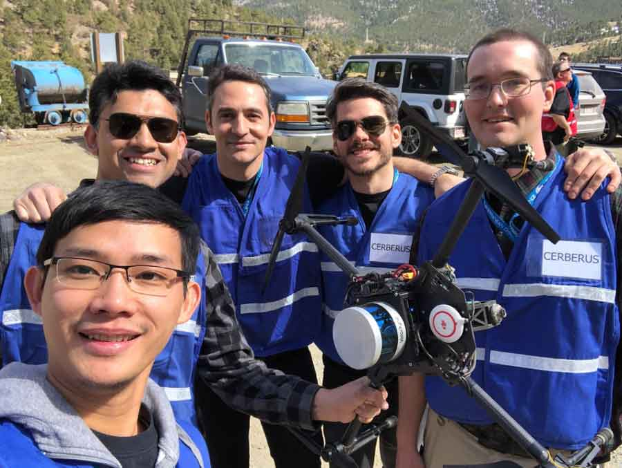A group of researchers in blue vests are posing with one of their robots during the DARPA competition.