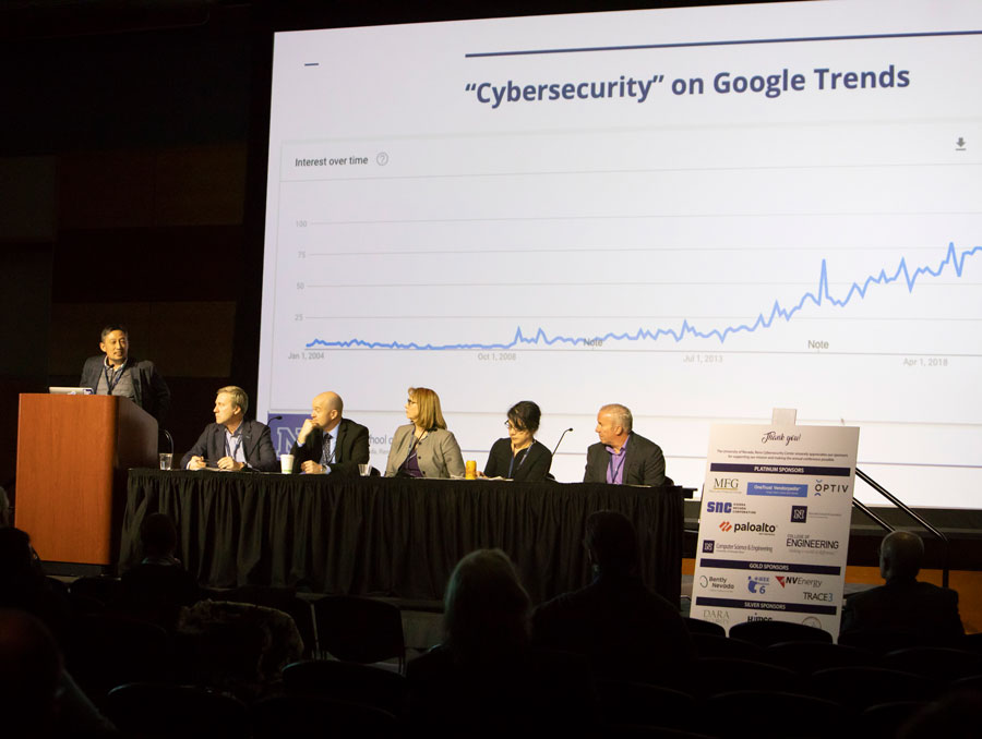 A panel of speakers sit in front of a presentation with a graph on it.