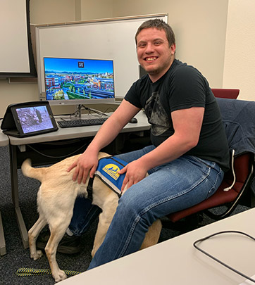 Student in a computer lab with seeing eye dog
