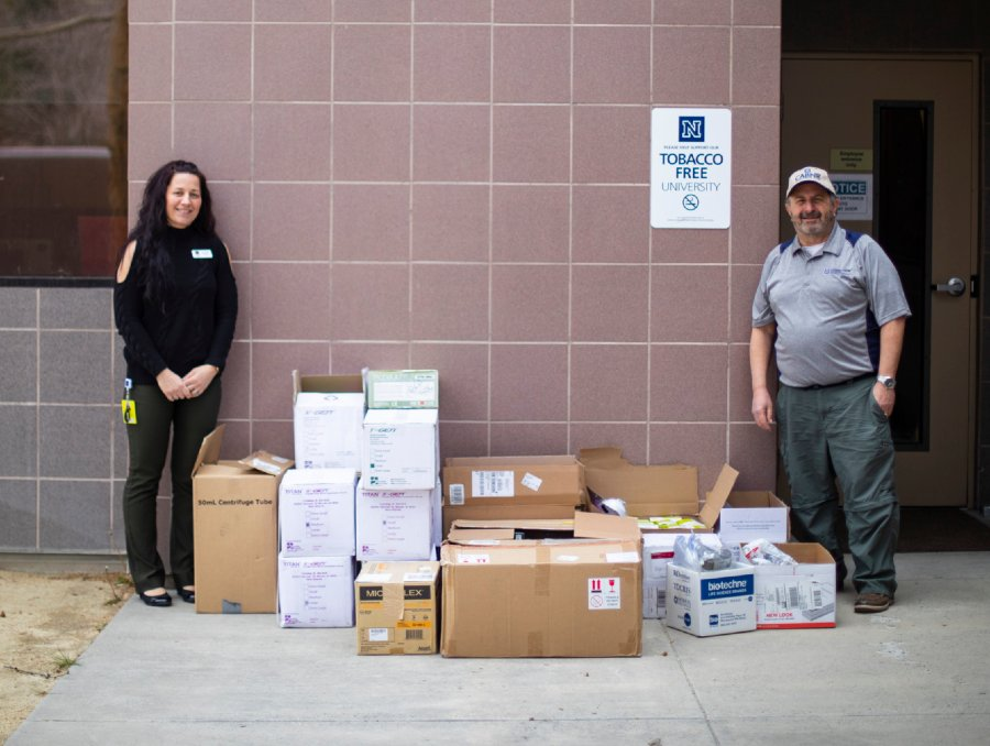 Jennie Parker and Chris Pritsos standing beside delivered personal protective equipment supplies
