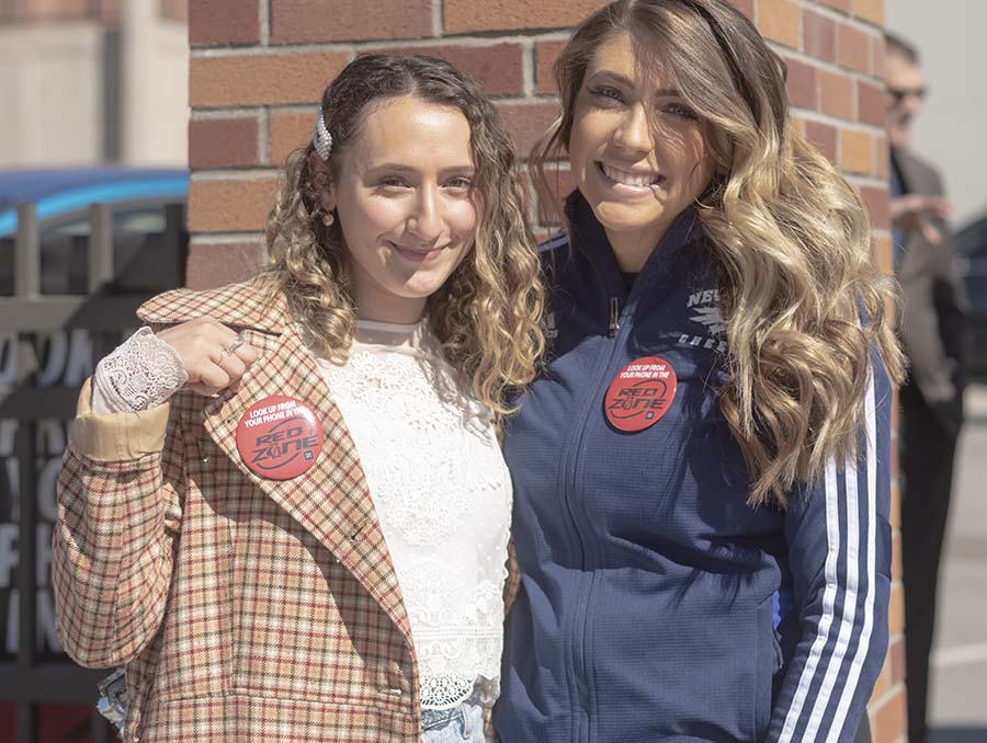 Students Claudia Feil, left, and Haley Cheatwood pose for a photo with Red Zone buttons on during the Red Zone campaign kick-off event.