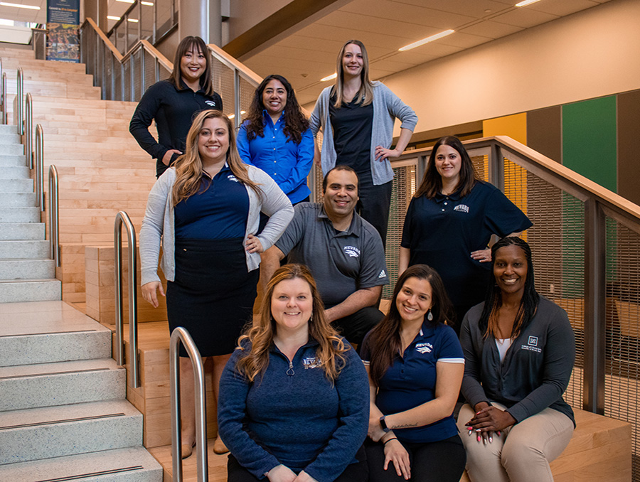 College of Liberal Arts advising team sits on stairs in Pennington Achievement Center