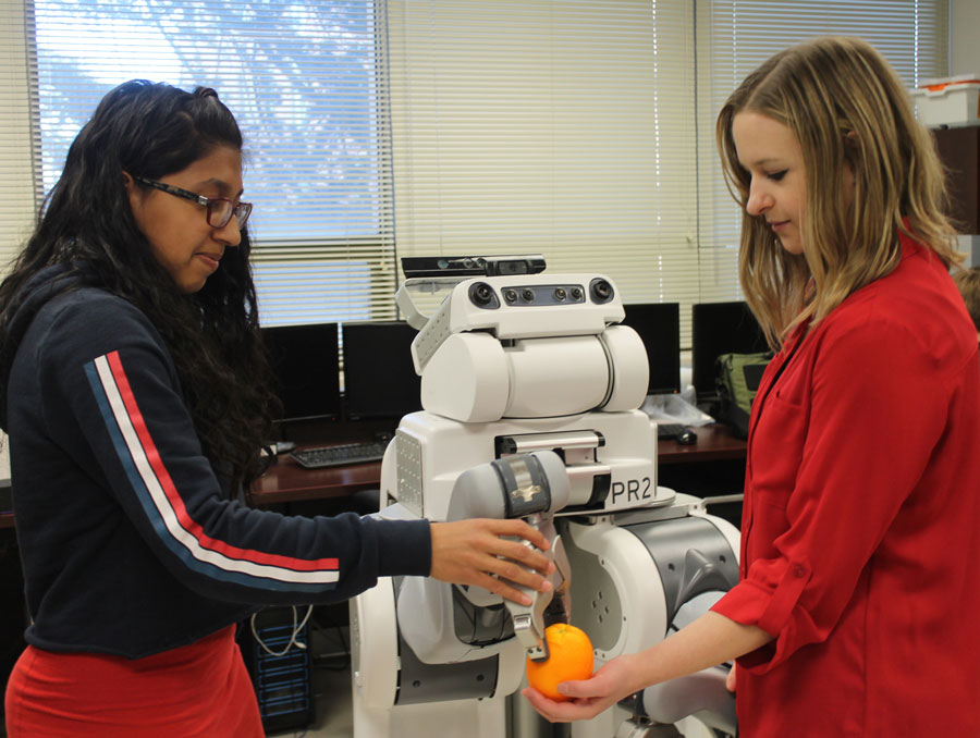 Eloisa Burton and Janelle Blankenburg pose with one of their research robots.