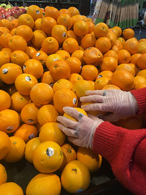Shopping Angels volunteer picks out oranges with gloved hands while grocery shopping
