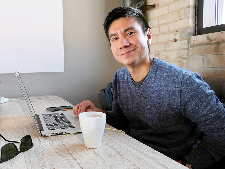 Ricardo Lopez sitting at a table with a cup of coffee and his laptop
