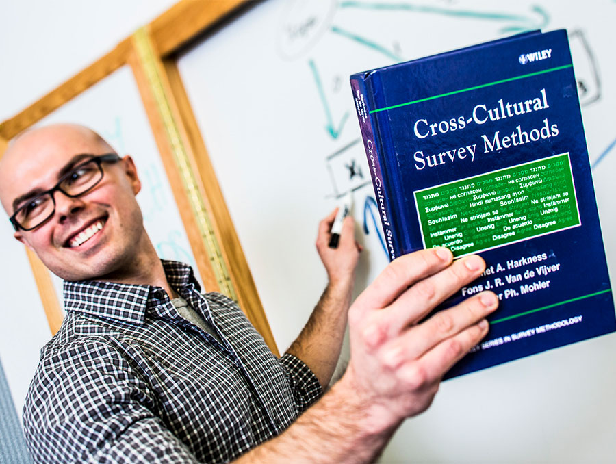 "Instructor teaching in front of a whiteboard while holding a textbook titled, ""Cross-Cultural Survey Methods"" by Harkness, Van de Vijver, and Mohler."