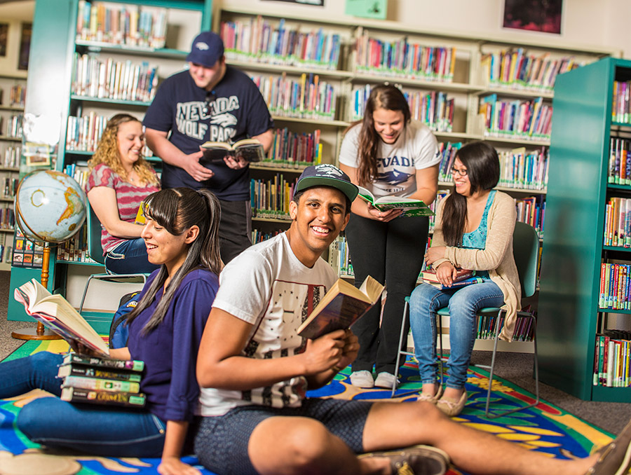 Group of students in a library reading books and interacting with each other.