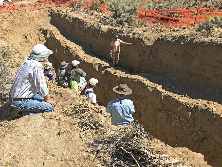 students studying earthquake trench