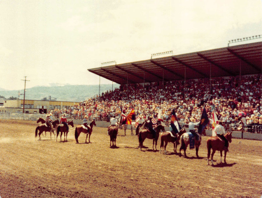 People ride on horses in an arena during the presentation of colors.