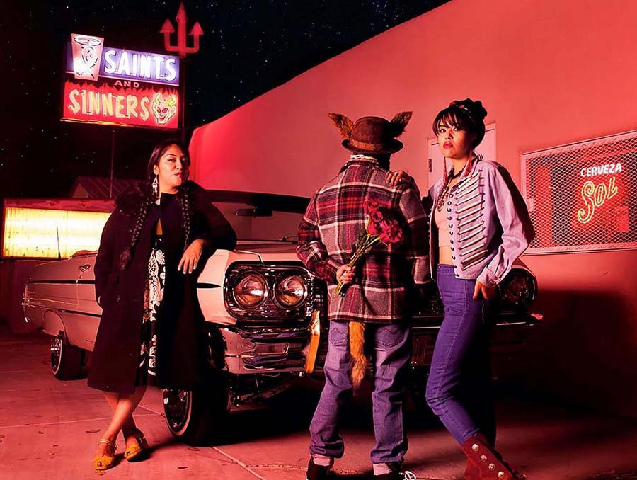 "Photograph by Cara Romero titled ""Coyote Tales,"" which includes a Saints and Sinners neon sign and three people standing outside a liquor store in front of a classic, convertible car."