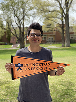 McNair Scholar Edward Cruz stands in the Quad at the University of Nevada, Reno holding a Princeton University flag