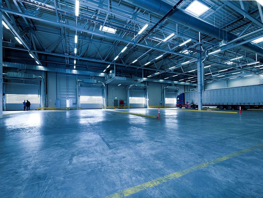 Large, mostly empty warehouse with one semi truck in the right corner.