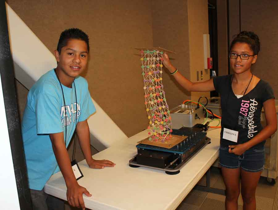 Two children standing near a table, which has a tower made of gumdrops on it.