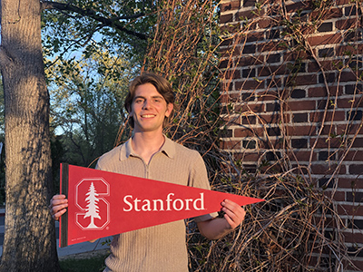 McNair student scholar Guglielmo Panelli stands holding Stanford flag