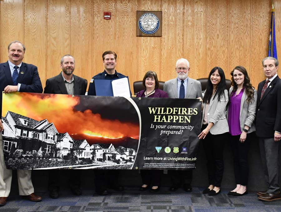 Carson City mayor holding a Nevada Wildfire Awareness Month banner alongside fire department and Living With Fire staff