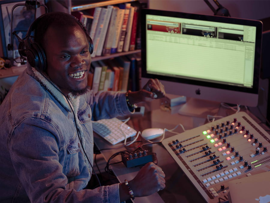 Robert Apiyo, also known as Prince Nesta, sitting in front of a computer and sound mixer.