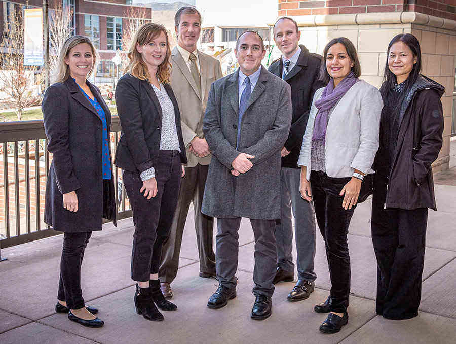 Teaching & Learning Technologies and the Instructional Design Team stand in a group on the landing out front of the main entrance of the Mathewson-IGT Knowledge Center.  From left to right: Kathy Hanselman, Kari Johnson, Don Massie, Ed Huffman, Bowen Drewes, Lia Schraeder and Wenzhen Li.
