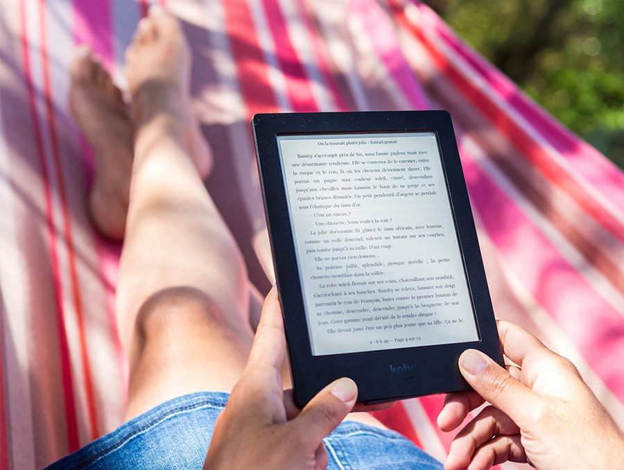 Woman laying in hammock reading a nondescript ebook on an ereader device