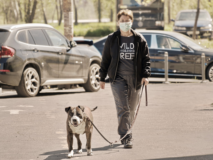 a woman wearing a mask while walking a dog