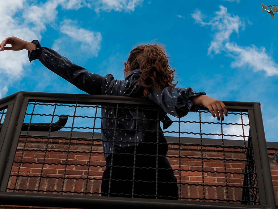 A person leans on an open staircase with their back to the camera looking up toward the blue sky. Photo by Caitlin Bell.