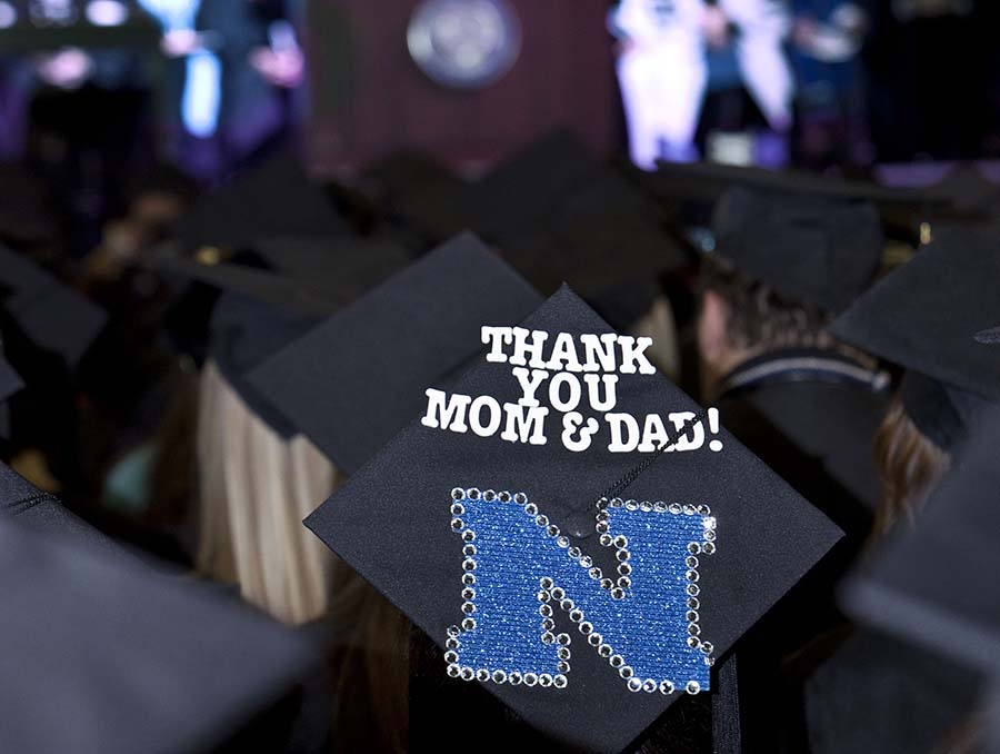 Thank you Mom & Dad! written on a black mortar board commencement cap at an indoor graduation ceremony.