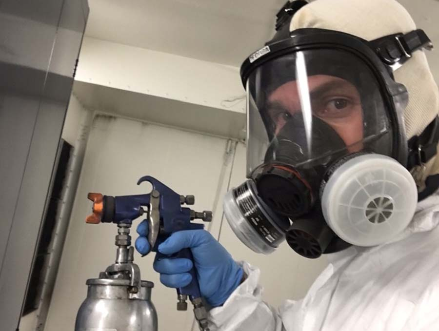 Man with a paint can and ventilated mask.
