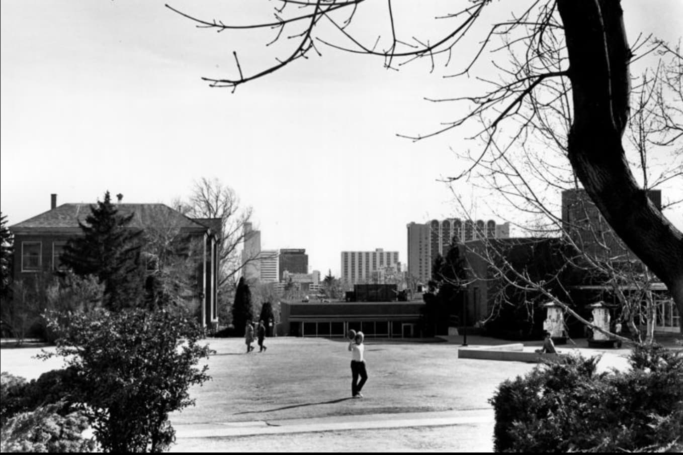A student stands on the lawn in front of the Jot Travis while throwing a ball in 1985.