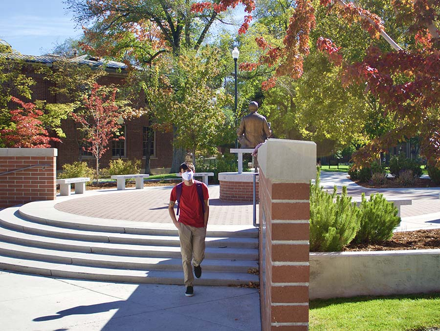 A student wear a facial covering walks through the University of Nevada, Reno campus with stairs and a statue behind them.