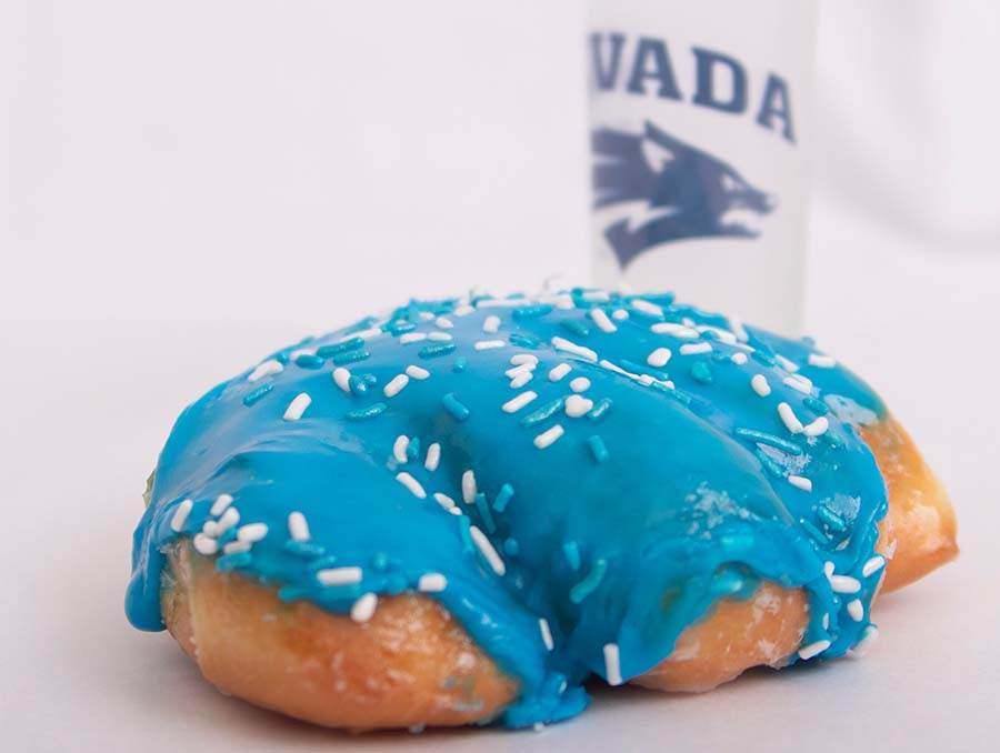 Blue Wolf Pack Paw donut with a white Nevada logoed water bottle.