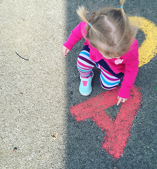 "Child pointing to the letter ""A"" written in chalk on concrete"