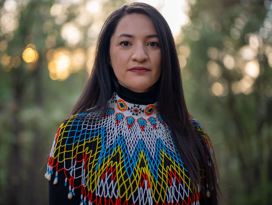 Tsanavi Spoonhunter stands in front of a forest backdrop wearing a Native American beaded collar.