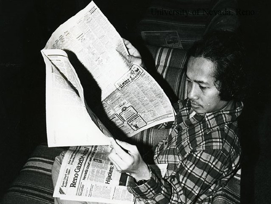 Unidentified University of Nevada, Reno student reading a newspaper while sitting on a couch