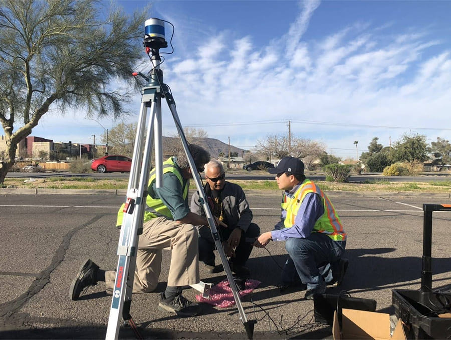 Three workers setting up a roadside LiDAR sensor