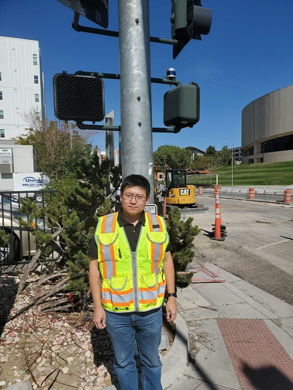 person in construction gear standing in front of streetlight with LiDAR sensor
