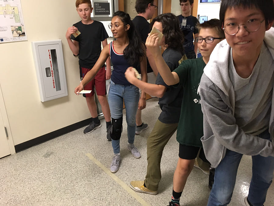 students in line in hallway preparing to throw items
