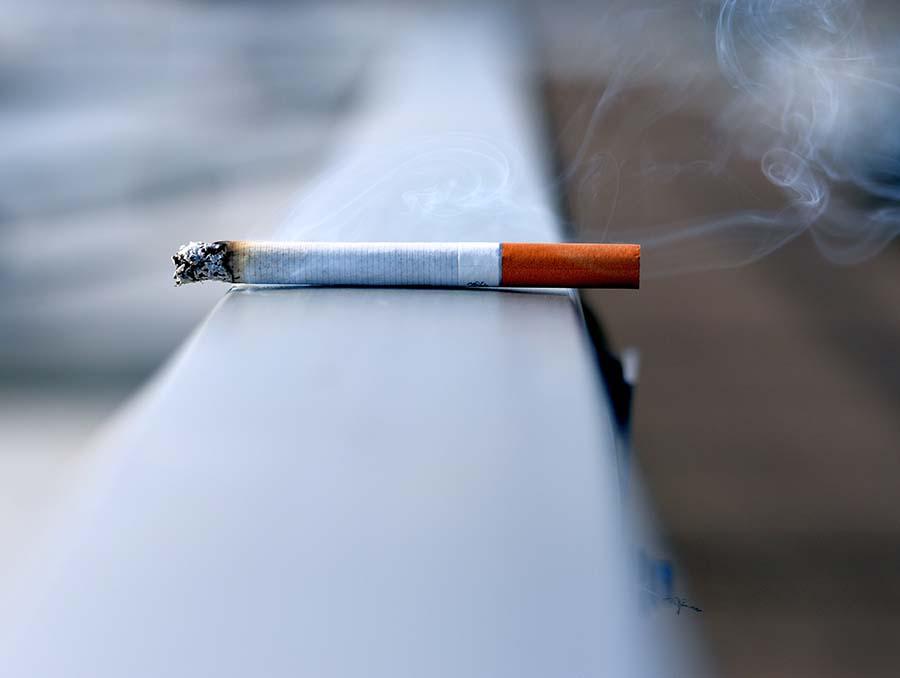 white cigarette burning on white wall