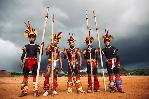 A group of men stand in front of a cloudy sky holding spears and wearing body paint.