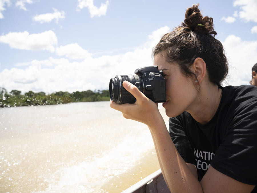 Luiza Vieira holds a camera to her face in front of a beach with greenery and the sky in the backdrop.